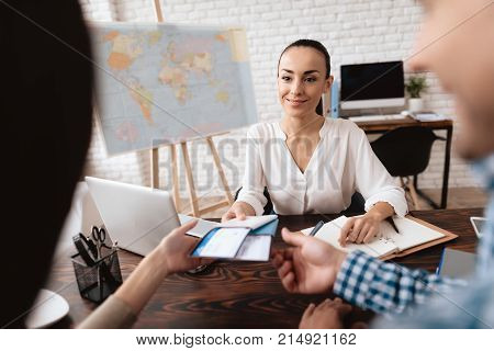 A young man and a woman came to the travel agency. They want to go on a trip during their holidays. The girl agent offers them different countries. She gives them tickets.