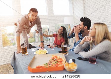 The company of young people play the game with stickers on the forehead. They play in associations. They are all friends and they are very cheerful. On the table are glasses with alcohol.