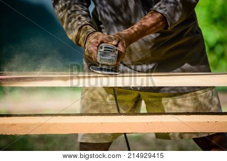 Joiner works with an electric scrubber and processes wooden products.Carpenter with handheld electric scrubber in the hands on the woodwork.Worker is scrubbing wood plank with handheld electric scrubber.