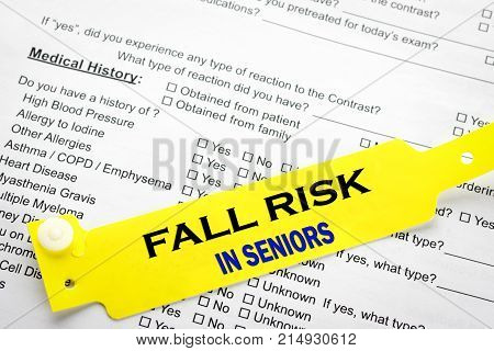 A yellow fall risk senior patient bracelet on top of a hospital questionnaire paperwork