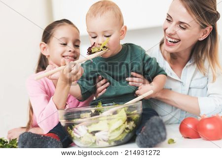 Mom and daughter have fun while preparing a salad. They are in a bright kitchen. Baby boy helps mom and sister to prepare salad.