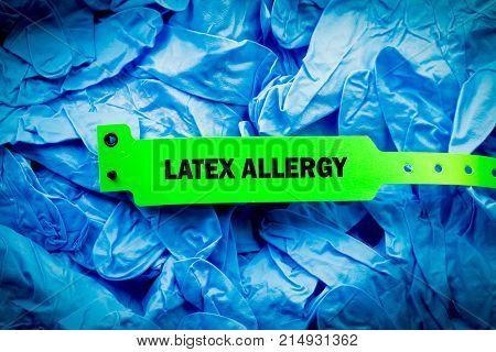 Green latex allergy bracelet over top blue protective gloves