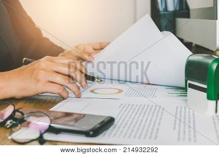 Close-up Businesswoman Reading And Checking Turnover Documents On Her Desk, Businiess Sheets Concept