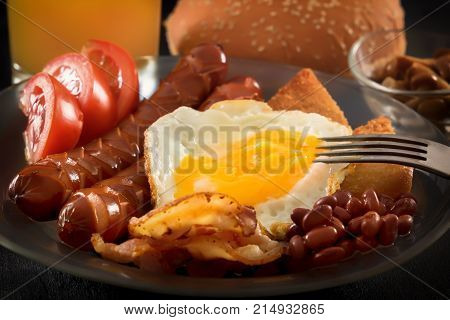 Full English breakfast with scrambled eggs, bacon, sausage, beans, tomatoes and juice. fork pierces the egg yolk. Black background