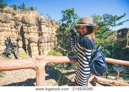 Young asian woman traveler travelling to wonderful soil cliff Pha Cho at Mae Wang National Park Doi Lo district Chiang Mai Thailand.