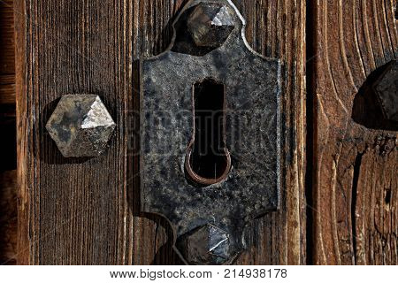 Closeup of an isolated rusty floral shaped keyhole on splintered grey wooden door