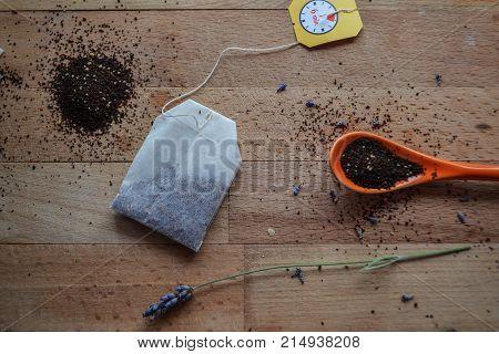 Tea bag, tea powder, tea granules in orange spoon at light wooden table/ conceptual image of tea time