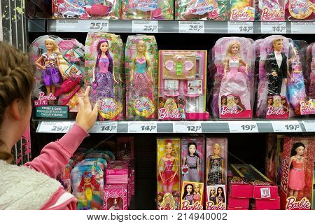 GERMANY - AUGUST 12, 2017: Shopping girl and Toy dolls in a store. Barbie is a fashion doll manufactured by the American toy company Mattel
