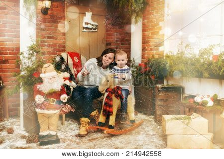 Young happy mother with cute little child boy on rocking horse in decorated New Year room with Santa at home. Christmas good mood. Lifestyle family and holiday 2018 concept. Magical highlight effect.