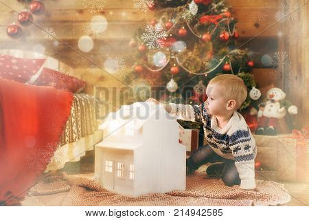 Happy Little Baby Boy Sitting At The Christmas Tree With A Toy White House In Wooden Room At Home. C