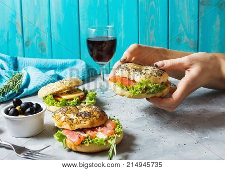Bagels with salmon vegetables cream-cheese and glass of red wine on grey concrete background. Woman hands hold bagel.