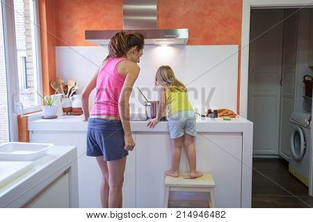 Little Child Cooking With Mother Supervising