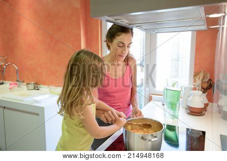 Woman And Child Cooking Together In The Kitchen