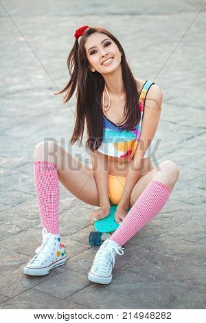 Attractive sporty asian woman in swimsuite smiling and sitting with skateboard on sidewalk in city park. Sport and summer holiday concept portrait. Gorgeous playful model posing with board. Young happy girl in bikini looking at camera.