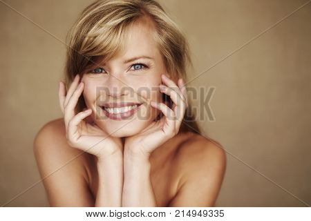 Gorgeous smiling young woman with hands on chin portrait