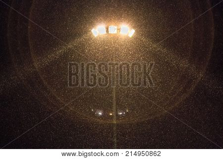 Magic Light From A Lighting Mast At Night Against A Background Of Falling Snow