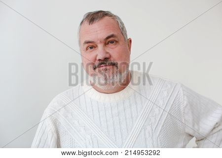 Middle aged bearded man looking at camera and smiling. Portrait of an adult male on a white background