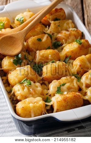 Delicious Baked Tater Tots With Cheese, Meat And Greens Close Up In A Baking Dish. Vertical