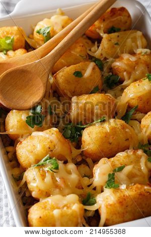 Casserole Of Tater Tots With Cheese And Herbs Close Up In A Dish Baking Dish. Vertical