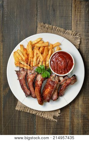 Grilled sliced pork ribs tomato sauce and french fries on white plate top view