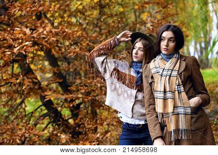 Fashion Portrait Of Two Beautiful Women Standing On Bank Of Autumn Landscape. Trendy Indian Coat And
