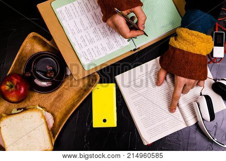 A man reads translates the text. Sandwich headphones pencils notebooks. Still life black background.