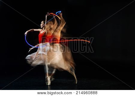 Gracious movements. Professional elegant female dancer moving her hands and dancing while performing on stage