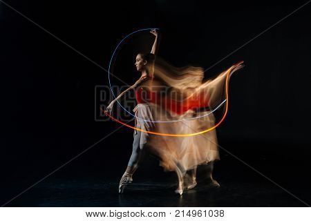 Dance studio. Serious well built female dancer standing against black background and practicing her movements while visiting dance studio