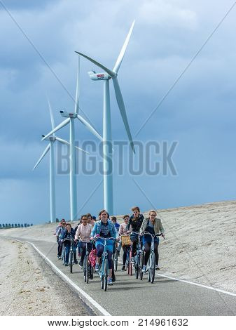 Zuid Holland the Netherlands - May 14 2016: young cyclists on a dike with wind turbines