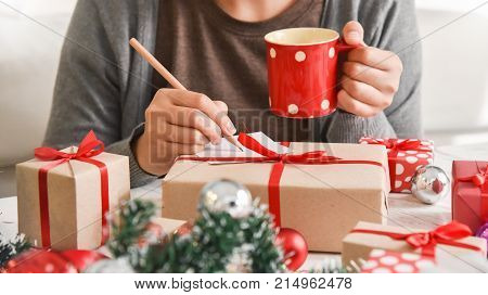 Female Hand writing greeting card with red and brown gift boxes for Christmas and New year. Holding cup of coffee.