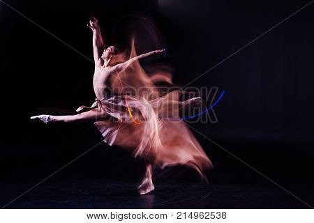 Wonderful skills. Attractive nice skillful woman making a jump and doing the splits in the air while showing her flexibility
