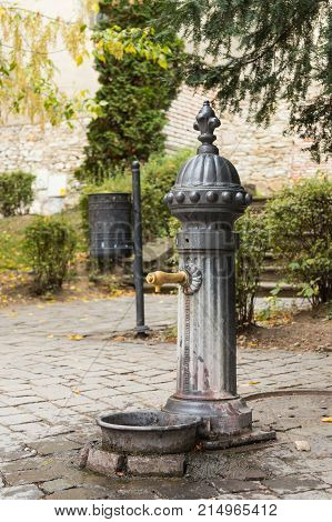 Sighisoara, Romania, October 08, 2017 : A water column with drinking water in the courtyard of the castle in Sighisoara city in Romania
