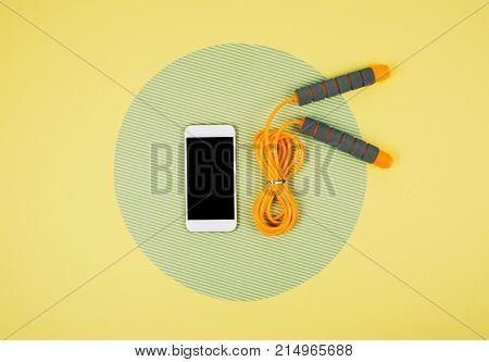 Orange Jump Rope With Smartphone On Yellow And Green Background.