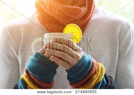 A young man holding a Cup of tea and lemon. Cold cold disease.