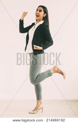 Full length portrait of cheerful young pretty Indian business woman standing on one leg and pumping fists. Isolated side view on white background.