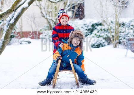 Two kid boys enjoying sleigh ride during snowfall. Children sledding on snow. siblings riding a sledge. twins play outdoors. Friends sled in snowy winter park.