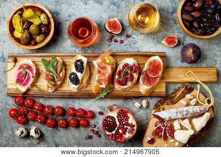 Appetizers table with italian antipasti snacks and wine in glasses. Brushetta or authentic traditional spanish tapas set cheese variety board over grey concrete background. Top view flat lay