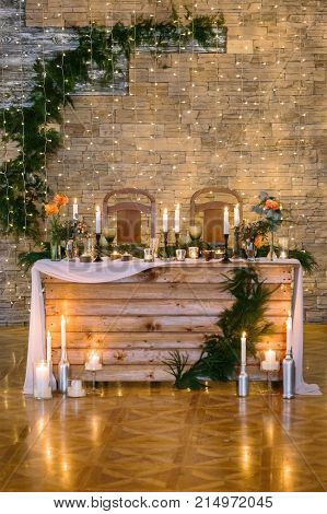engagement, celebration, feast concept. place for newly wed couple of lovers in the reastaurant hall that is decorated with numerous of candles and twinkle lights, flowers and conifers branches
