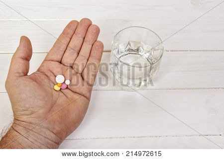 Healthcare treatment supplements concept photo. Man arm holding heap of small round meds and glass of water before taking medication focus on medicine.