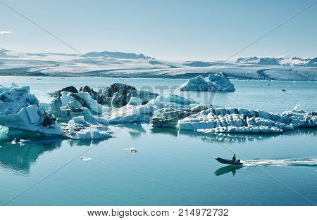 Beautiful vibrant picture of icelandic glacier and glacier lagoon with water and ice in cold blue tones, Iceland, Glacier Bay, icebergs in the water and in the lagoon a motor boat is floating