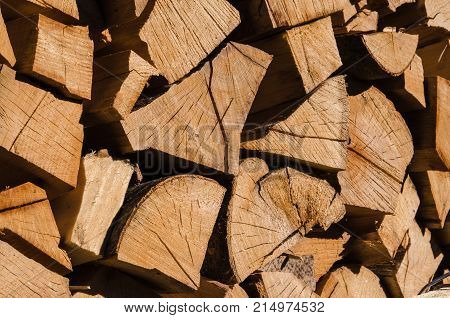 A pile of stacked firewood, prepared for heating the house. Firewood harvested for heating in winter. Chopped firewood on a stack. Firewood stacked and prepared for winter Pile of wood logs. High-quality wood, cut and stacked.