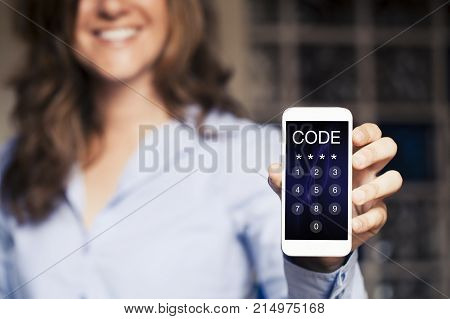Smiling woman holding a mobile phone with passcode in the screen.