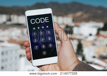 Man holding mobile phone with passcode in the screen. Unlocking phone.