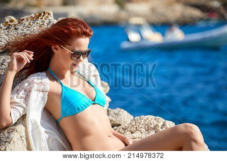 Redhaired woman in bikini relaxed on quiet sea with warm sun colors.