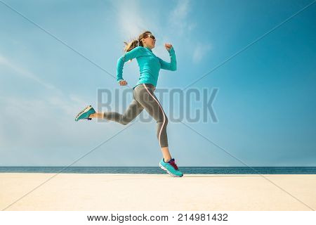 Woman running along the sealine coast under sunlight at sunny summer day.