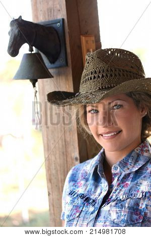 Portrait of young country girl in western hat outside of country house, looking at camera, smiling.