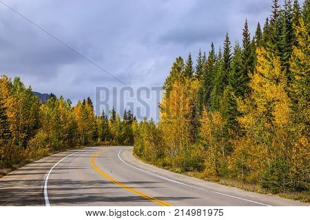 Heavy storm clouds over the mountains. Yellow and evergreen forests along the road 93