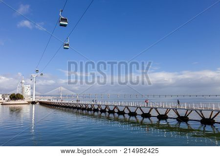Parque das Nacoes, Lisbon, Portugal - February 01, 2017: People walking and running. Passeio Ribeirinho on Tagus River. Seen the Vasco da Gama Tower, Bridge, Myriad Hotel, aerial tramway. Nations Park