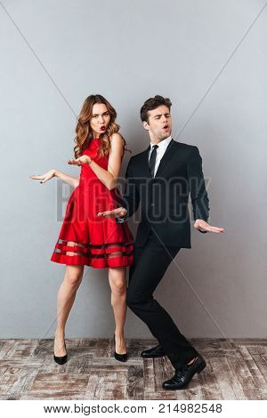 Full length portrait of an attractive happy couple dressed in formal wear dancing together and having fun over gray wall background