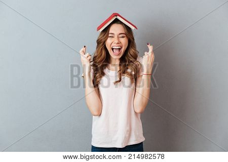 Portrait of a cheerful happy girl holding book on her head with crossed fingers for good luck isolated over gray wall background